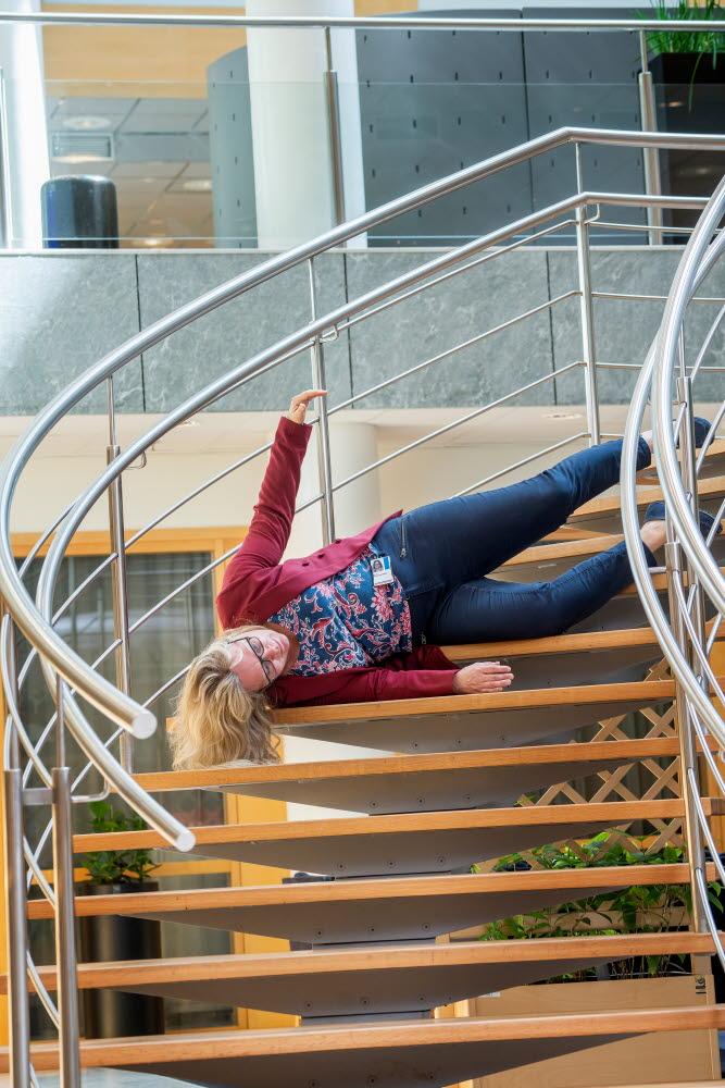 Kvinna faller i en trappa inomhus.